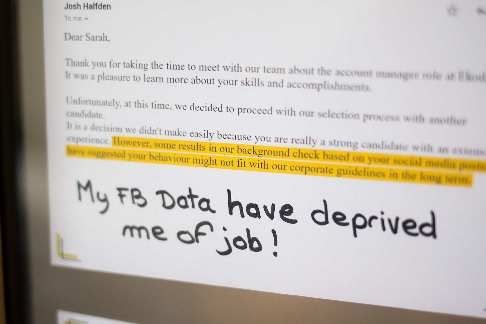 A close-up on a card of the anti-memorial: a rejection email for a job application due to a background check on social media